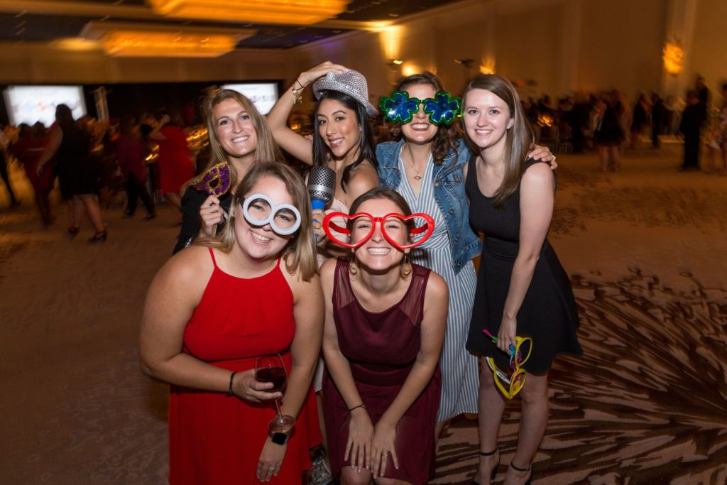 6 women in formal dresses posing with funky glasses and photo booth props